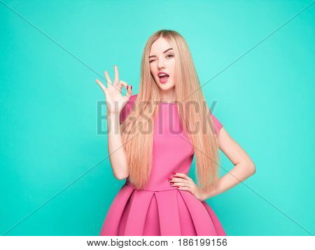 The beautiful young woman in pink mini dress posing at the studio on blue background.