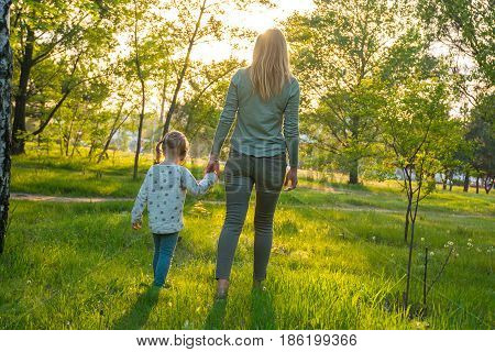 Young Mother With Her Amusing Daughter Are Walking Through Park