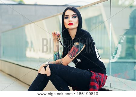 Tattoed Beauty. Portrait Of Beautiful Tattoed Hipster Girl Posing To Camera While Sitting Against Ur
