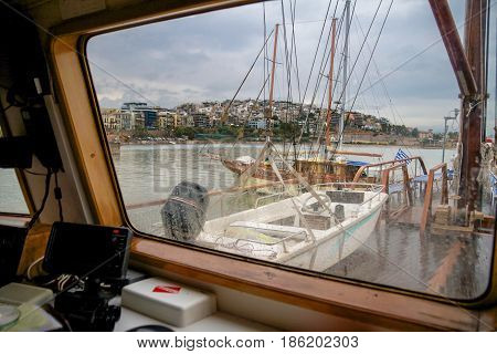 view of the deck of a ship and Kastela city of Piraeus during a rainy day through glass with water drops. Greece