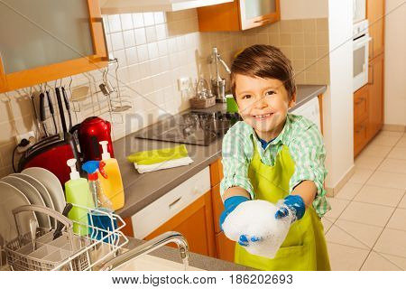Portrait of smiling kid boy wearing rubber gloves and playing with foam during dishwashing in the kitchen