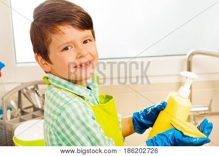 Close-up portrait of smiling kid boy in rubber gloves pouring dish soap from blanked plastic bottle on a sponge in the kitchen
