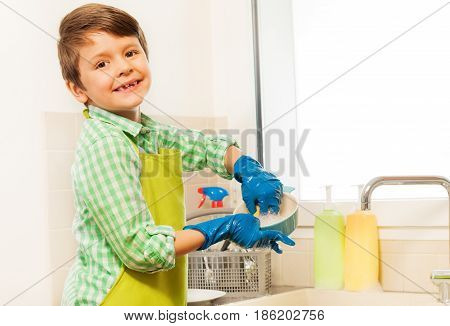 Portrait of happy six years old boy in rubber gloves learning to wash dishes in the kitchen