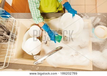 Top view picture of kid doing the dishes with sponge in foamy sink in the kitchen