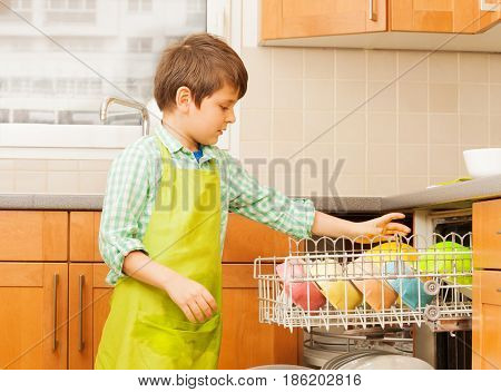 Kid boy in apron getting out clean and dry crockery of dishwasher in the kitchen