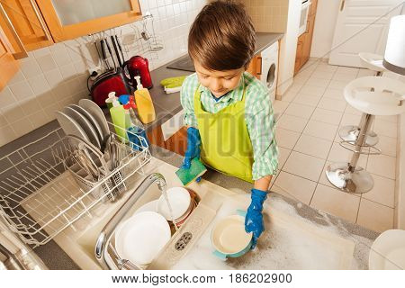 Kid boy in rubber gloves sponging bowls and plates under running water in the sink