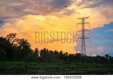 High voltage electric transmission tower during golden hour sunset.