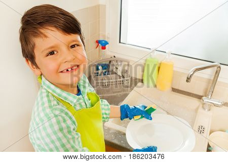 Close-up portrait of smiling kid boy washing dishes with sponge standing next to the sink
