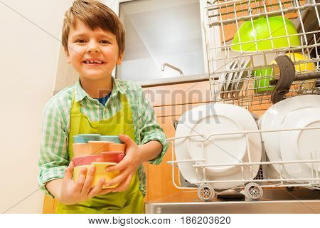 Happy boy holding clean bowls standing next to the opened dishwashing machine