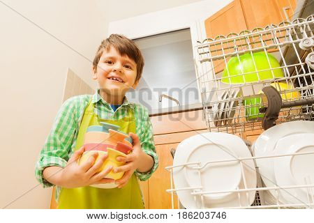 Portrait of six years old boy loading dirty dishes to dishwashing machine
