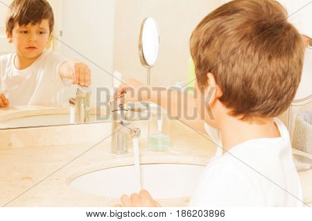 Six years old boy turning tap on standing next to the sink in the bathroom