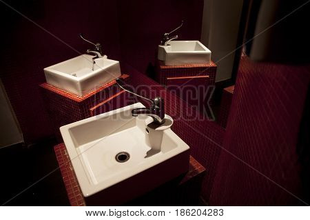 White washbasins in the red bathroom of a restaurant