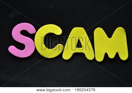 word scam on a abstract black background