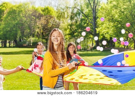 Portrait of beautiful fair-haired girl holding rainbow parachute and playing with friends in the park