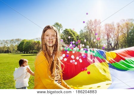 Portrait of beautiful fair-haired girl playing parachute games with her friends outdoors at sunny day