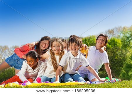 Big group of happy 10-12 years old kids, sitting on the lawn in the park, hugging and laughing