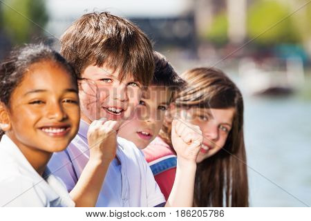 Close-up portrait of happy multiethnic kids, 10-12 years old boys and girls spending holidays outdoors
