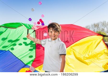 Portrait of happy Caucasian boy playing with a colorful parachute outside at sunny day