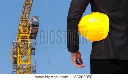 back view of construction manager with yellow safety helmet business industrial concept on yellow construction tower crane with blue sky background.