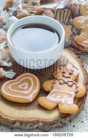Sweet gifts for hollydays. Homemade christmas gingerbread cookies and cup of coffee on wooden board vertical.