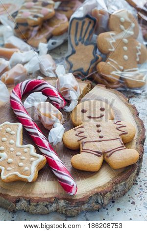 Sweet gifts for hollydays. Homemade christmas gingerbread cookies and caramel candies on wooden board vertical.