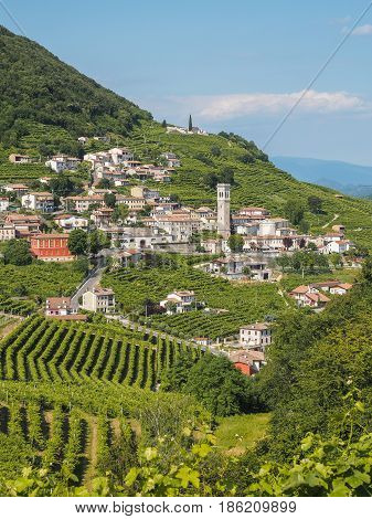 Small town of Valdobbiadene surrounded by vineyards zone of production of traditional italian white sparkling wine Prosecco. Vertical frame.