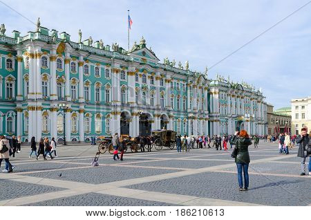 SAINT PETERSBURG RUSSIA - MAY 1 2017: Unknown people are walking along Palace Square near State Hermitage Museum (Winter Palace) St. Petersburg Russia