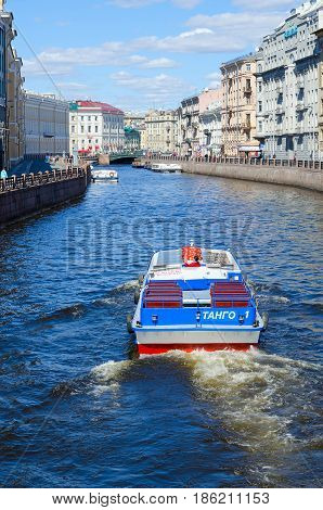 SAINT PETERSBURG RUSSIA - MAY 3 2017: Excursion ships on Moika River near Green Bridge in St. Petersburg. Unidentified tourists are visiting sights during walk along rivers and canals of city