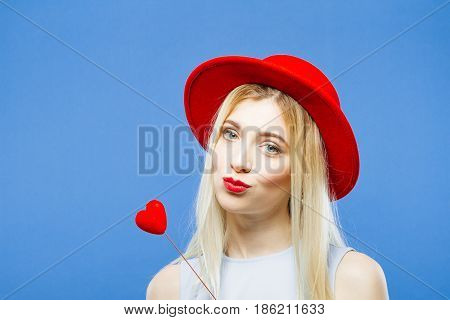 Amazing Young Blonde with Hat and Little Red Heart in Hands is Grimacing Looking at the Camera on Blue Background in Studio. Valentines Day Concept.