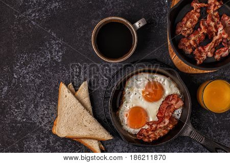 Breakfast with bacon fried egg coffee and orange juice top view copy space.
