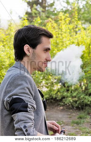 Laughing young businessman smoking a vape in the park