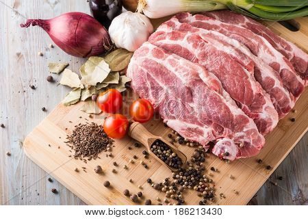 Horizontal photo with several slices of pork meat from neck. Meat has a fat on side. Several spices as pepper are spilled around with salt. Vegetable and balsamic vinegar is around.