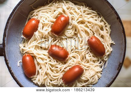 Sausages with pasta in vintage frying pan
