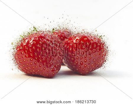Three fresh ripe red strawberries exploding on white