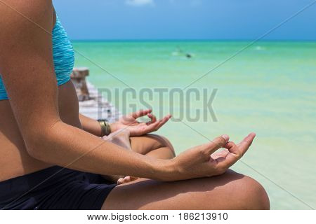Closeup of woman's hand in meditation in a Caribbean island. Holbox, Mexico.