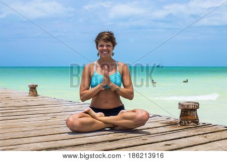 Yoga teacher in a wooden pier in a Caribbean island. Holbox, Mexico.