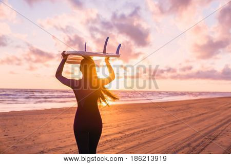 Beautiful young woman surf girl in wetsuit with surfboard on a beach at sunset or sunrise and ocean