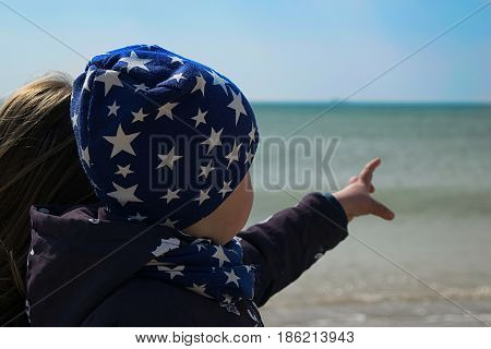 A young mother and a little boy of three years look at the sea on the beach and the kid points finger to the distance