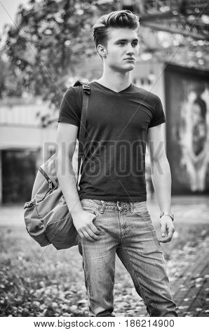 Attractive young man standing in city environment, with rucksack on one shoulder