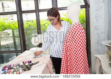Young female fashion designer workingdesigning clothes for puppets at studio on garment