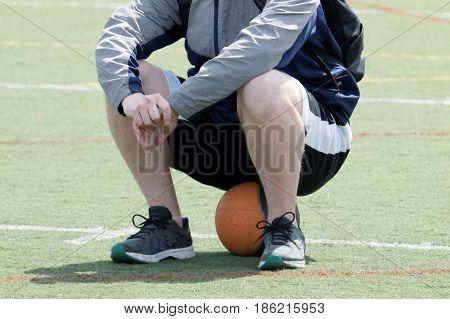 A man sits on a medicine ball on a green turf field