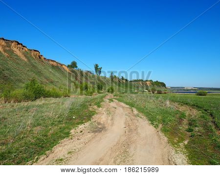 Rural, road, passing ,under ,a cliff in the lobe of the lake
