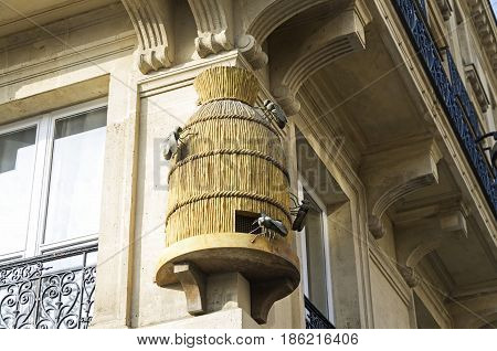 Decorative sculpture on the corner of the house - a beehive with bees. Paris France.