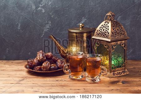 Lightened lantern tea cups and dates on wooden table over blackboard background. Ramadan kareem holiday celebration concept