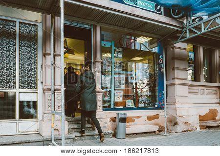 STRASBOURG FRANCE - FEB 3 2017: Two women entering french press kiosk with diverse advertising of newspapers and magazines in France