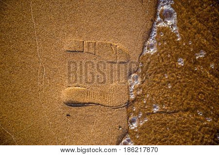 Footprints From Shoes On Wet Sand Washed Away By A Wave