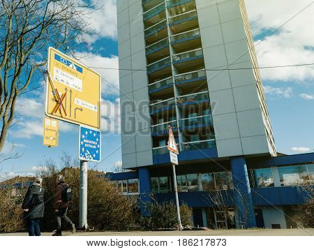 KEHL GERMANY - FEB 3 2017: Couple of senior German citizens walking under Deutschland signage at the border between Germany and France under the blue Bundesrepublik Deutschland sign