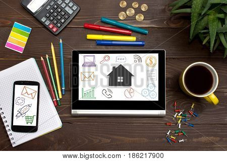 Tablet With Web Icon Home On A Wooden Table With Office Tools.the Concept Of Finding Housing For Ren