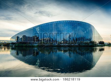 STRASBOURG FRANCE - MAR 31 2017: South facade of the European Parliament in Strasbourg with the intersection of the Ill and Marne-Rhine Canal at dusk. The European Parliament (or EU Parliament or the EP) is the directly elected parliamentary institution o