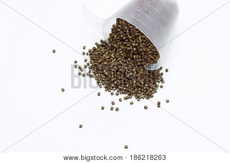 Plastic Pellets. Polymeric Dye Spilled Out Of The Measuring Cup On A Light Background . Colorant For
